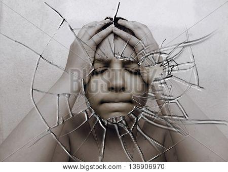 Sad boy on a background of broken glass.