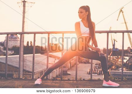 Warming up. Beautiful young woman in sports clothing doing stretching exercises and looking concentrated while standing on the bridge