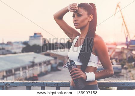 Feeling tired. Beautiful young woman in sports clothing holding bottle with water and looking tired while standing on the bridge with evening sunlight and urban view in the background
