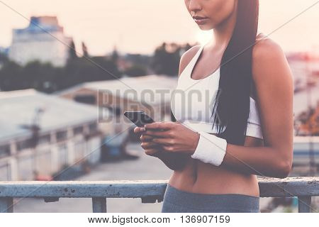 Recording her results. Close-up of beautiful young woman in sports clothing holding smart phone and looking at it while standing on the bridge with evening sunlight and urban view in the background