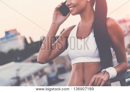 Good talk with friend. Close-up of beautiful young woman in sports clothing talking on the mobile phone and smiling while standing on the bridge with evening sunlight and urban view in the background