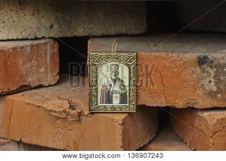 Saint Nicholas icon on red brick wall close up