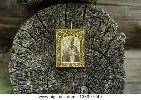 Saint Nicholas icon on grey wood blockhouse wall close up