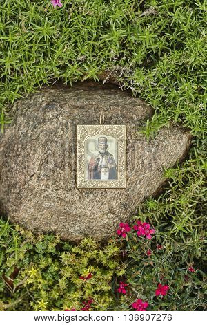 Saint Nicholas icon on grey big stone close up