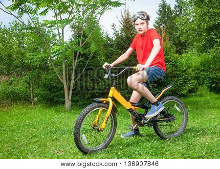 Cute teen boy wearing red tshirt and goggles sitting on a bicycle in a summer park looking at camera