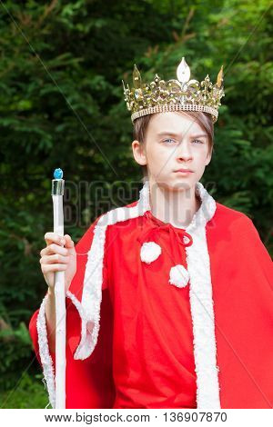 Cute teen boy wearing crown and red costume holding a scepter pretending to be a king