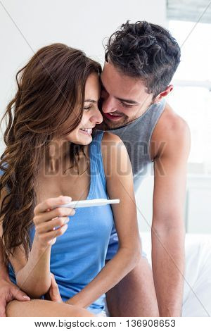 Happy romantic couple with pregnancy test on bed