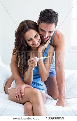 Happy young woman holding pregnancy test while husband embracing on bed in room