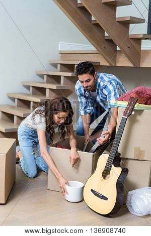Couple unpacking computer from cardboard box at home