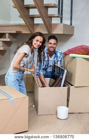 Portrait of smiling couple unpacking computer from cardboard box at home