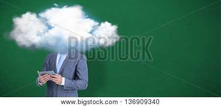 Businessman using tablet against green background