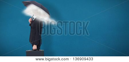 Businessman under umbrella while holding a briefcase against blue background