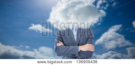 Midsection of businessman standing arms crossed against blue sky
