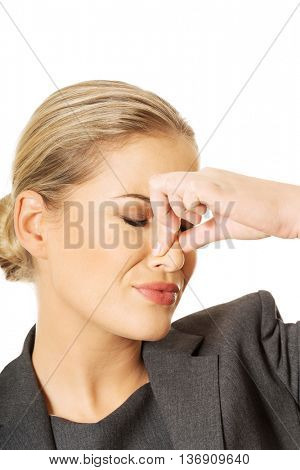 Woman pinching nose because of smell