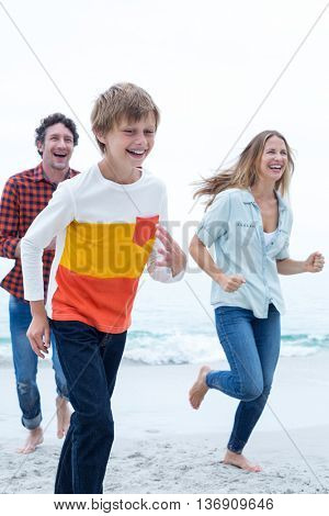 Cheerful family running at sea shore against sky