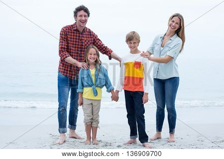 Full length of happy family standing at sea shore against sky