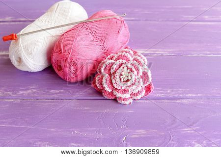 Home made pink and white crochet flower decorated with beads. Two skeins of cotton yarn and crochet hook on lilac wooden background. Easy and beautiful knitting idea