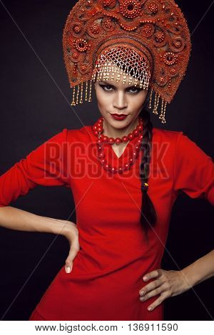 Woman posing in red dress and metal headwear on black background