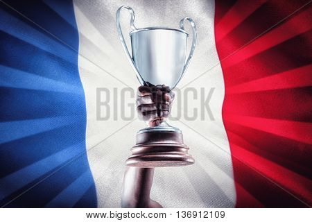 Happy sportsman looking up and cheering while holding trophy against digitally generated france national flag