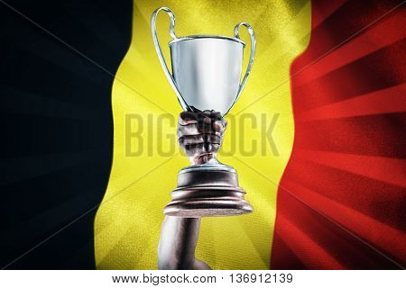 Happy sportsman looking up and cheering while holding trophy against belgium flag