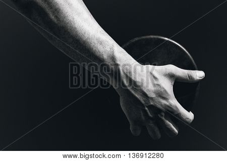 Close up of sportsman hand is holding a discus against black background