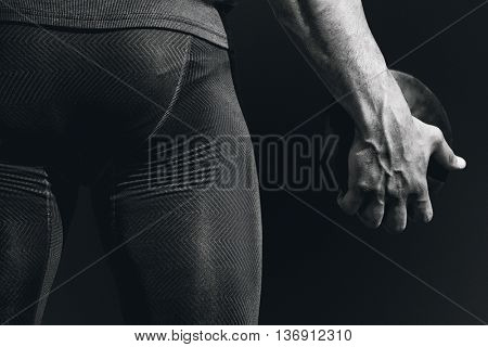 Rear view of sportsman holding a discus against black background
