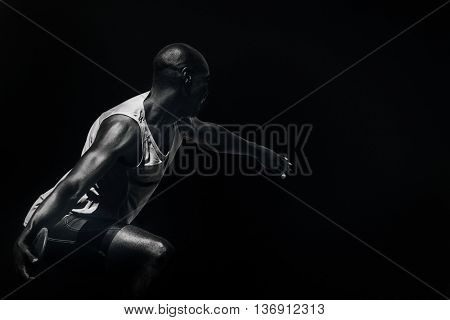 Rear view of sportsman throwing a discus against black background