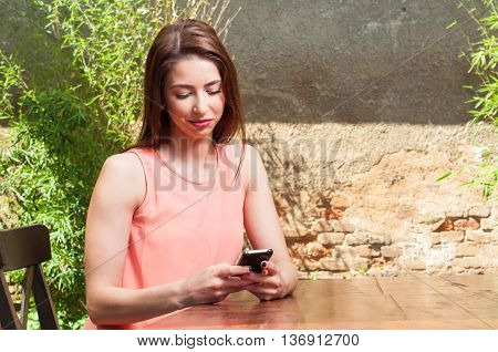 Woman Sitting On Terrace And Texting On Smartphone