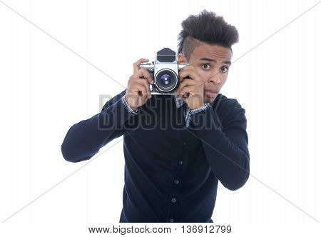 Young african man holding an old camera peeking on what he sees.