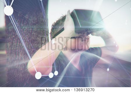 Futuristic blue background against elementary boy looking through virtual reality headset in school library