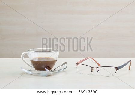 Closeup black coffee in transparent cup of coffee and eyeglasses on blurred wooden desk and wall textured background in the meeting room relaxation in coffee break concept by coffee and eyeglasses