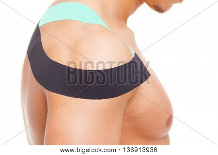 Fit man with kinesiotaping on the shoulder, isolated on white background