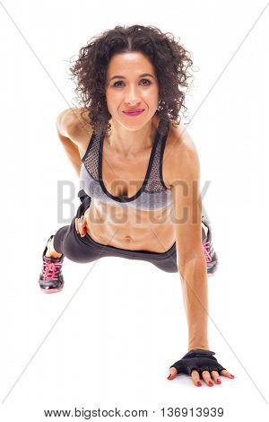 Fit woman making push ups with one arm, isolated on white background