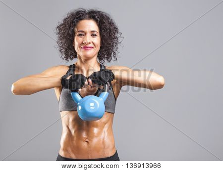 Fitness women lifting a kettle bell on grey background