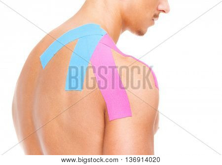 Muscular man with kinesiotaping on the shoulder and back, isolated on white background