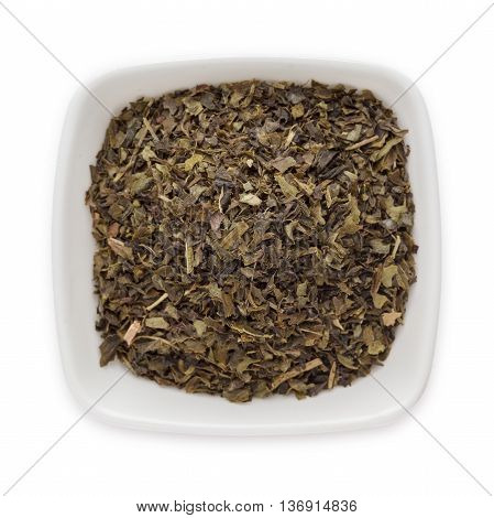 Organic Green tea (Camellia sinensis) Tea bag cut, dried leaves, in white ceramic bowl isolated on white background. Macro close up. Top view.