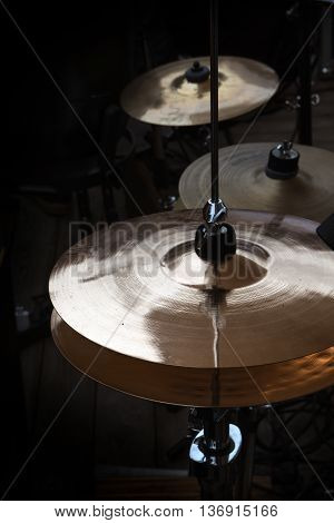 hi-hat and cymbals on stage musical instruments in a percussion drum kit for modern pop rock jazz folk music and more dark background vertical selected focus narrow depth of field