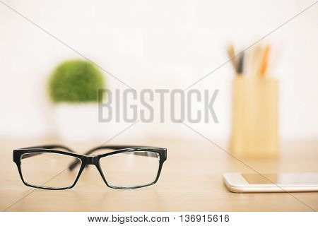 Closeup of glasses on blurry office desktop with stationery items smartphone and plant on blurry background