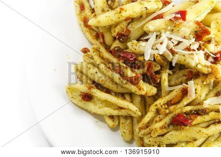 homemade pasta variety called capunti with aglio e olio which is garlic and oil thereto pickled tomatoes and parmesan cheese specialty from southern Italy closeup with view from above background fades to white