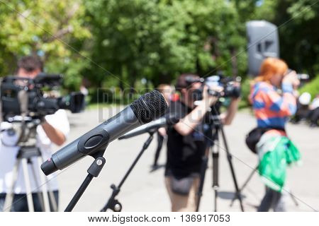 Microphone in focus against blurred camera operators and photographer
