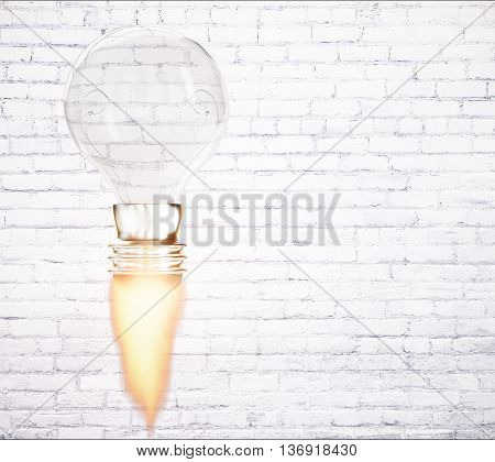 Business start up idea concept with abstract rocket fire lightbulb on white brick wall background with copy space. 3D Rendering