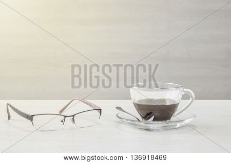 Closeup black coffee in transparent cup of coffee and eyeglasses on blurred wooden desk and wall textured background relaxation in coffee break concept by coffee and eyeglasses in art tone