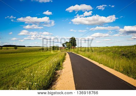 Cycle track in a field on a sunny day. Landscape with a beautiful cloudy sky in Waldviertel Austria. The road into the field.