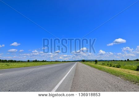 Straight empty road and roadside with cuttings grass running to horizon through meadows. Blue sky with white clouds and green hills on a background