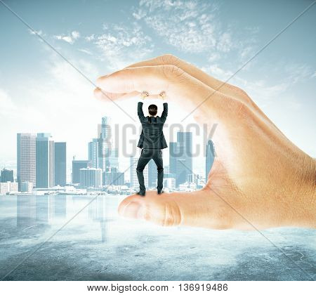 Businessman trapped between fingers of big hand on city background. Pressure concept