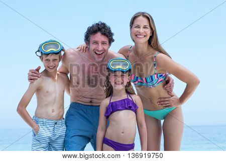 Portrait of happy family in swimwear standing at sea shore against sky