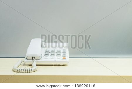 Closeup white phone office phone on blurred wooden desk and frosted glass wall textured background in room at the office