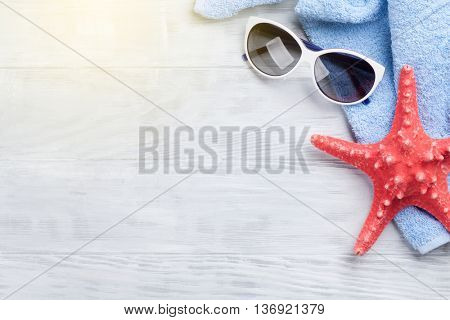 Beach accessories. Towel, sunglasses and starfish on wooden background. Top view with copy space. With sun beam