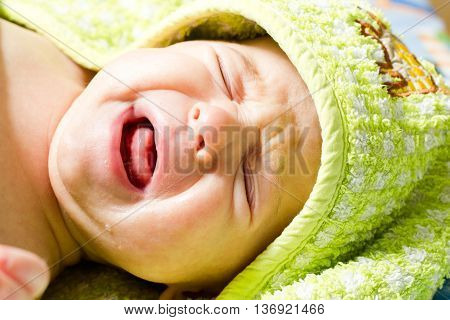 Crying baby. Newborn baby lying in a hooded towel after taking a bath and cry.
