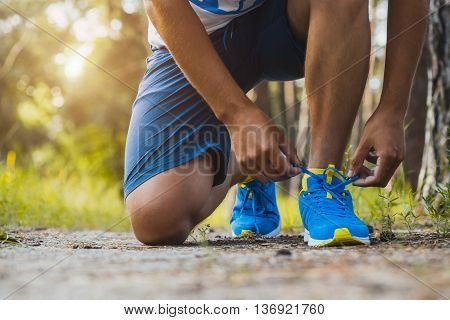 Runner tying shoelaces on sneakers. Morning jogging in the forest